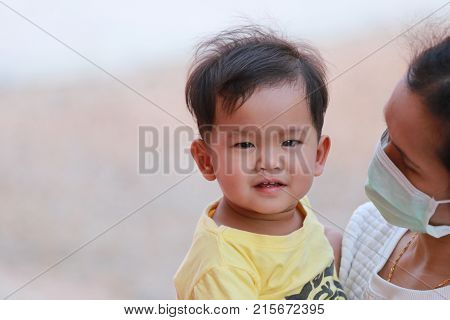 Asian boy in yellow dress in embrace your mother is carryingconcept of health care and love of the family.