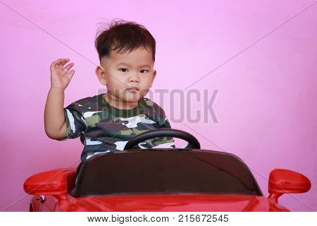 Asian boy driving a toy car and have pink wall background.