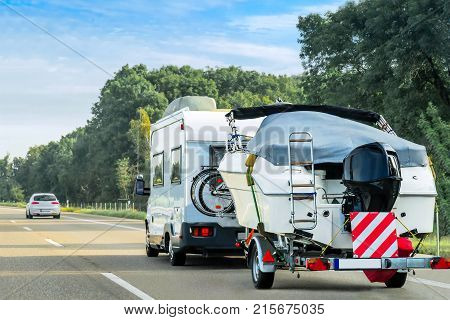 Caravan and trailer for motor boats on the road in Switzerland.
