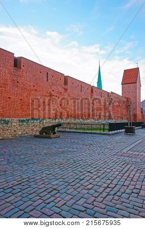 Riga Latvia - December 26 2011: Red brick defensive walls and cannons in the historical center in the old town in Riga Latvia.