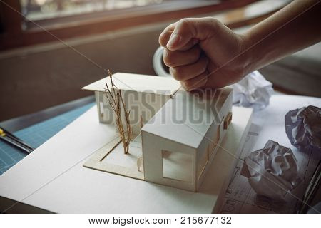 Closeup image of an angry architects try to destroy an architecture model on the table by hand while fail