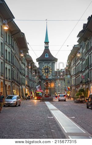 Bern Switzerland - August 21 2013: Zytglogge clock tower at Kramgasse street in old city center of Bern Switzerland. Illuminated late in the evening. People on the background