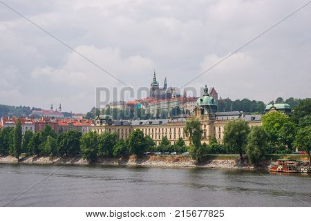 Vltava River embankment and Prague Old Town Czech Republic. Strakova Academy with Saint Vitus Church on the background
