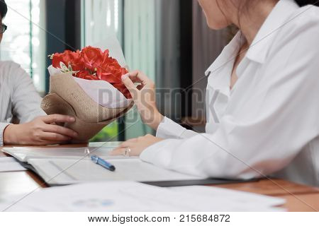 Cropped image of attractive young Asian woman accepting a bouquet of red roses from boyfriend in office on valentine's day. Love and romance in workplace concept.
