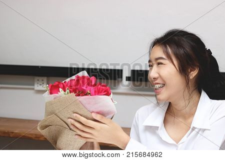 Cheerful young Asian woman accepting a bouquet of red roses from boyfriend in office on valentine's day. Love and romance in workplace concept.