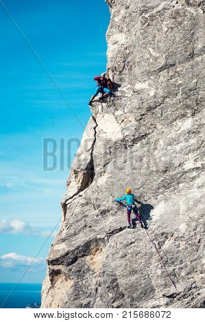 Photographer shoots climber. Athletes train on natural terrain. The photographer sits on top of a rock and looks at the woman. The man takes a picture of the climber on the camera.