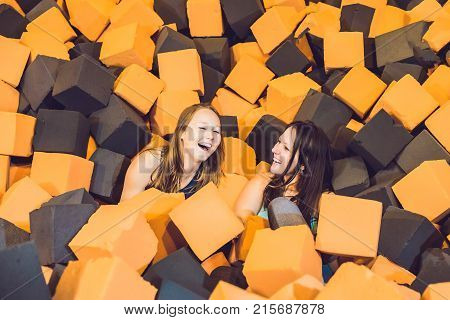 Two young women having fun with soft blocks at indoor children playground in the foam rubber pit in the trampoline center.