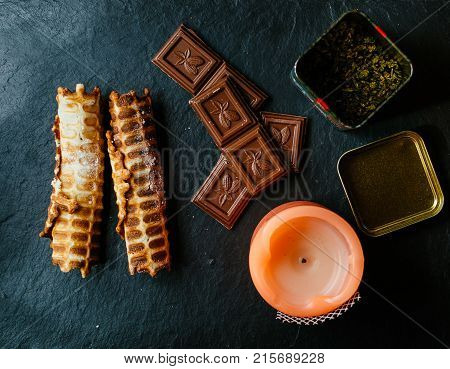 Chocolate, waffer tubes, candle and tea on the black board