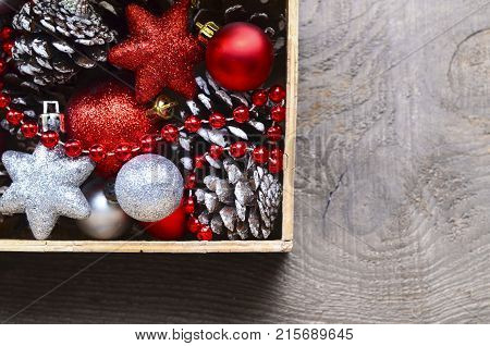 Christmas tree decoration: red and silver shiny balls,stars and pine cones in a vintage wooden box.Prepare for Christmas Eve or New Year winter holidays.