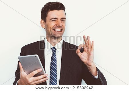 Portrait of cheerful young Caucasian businessman holding pc tablet, winking at camera and showing ok sign