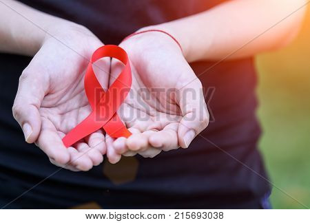 Woman hands holding red AIDS awareness ribbon. World Aids Awareness campaign.