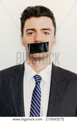 Portrait of young Caucasian businessman wearing suit looking on camera with adhesive tape on mouth. Censorship concept