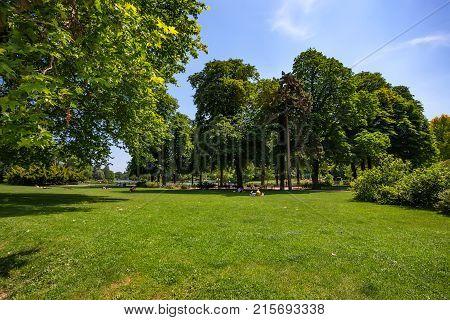 View of people resting in sunlit Bois de Vincennes in Paris