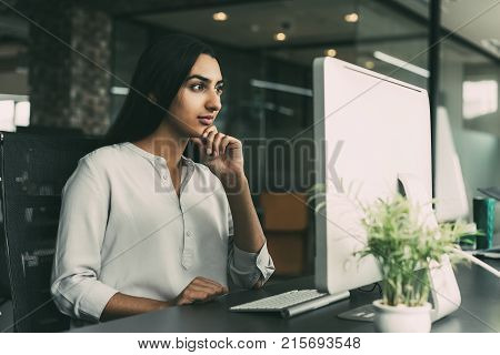 Portrait of confident young Latin-American businesswoman sitting at table in office and working with computer. Woman looking at monitor with hand on chin