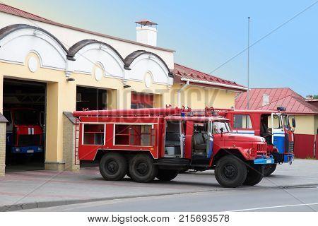 Two fire trucks near a fire station
