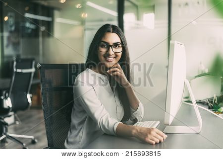 Portrait of young Latin-American executive wearing glasses sitting at her workplace with computer in office, looking at camera with hand on chin and smiling