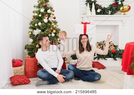 Happy Young Cheerful Parents With Cute Little Son. Child Boy Sitting In Light Room At Home With Deco