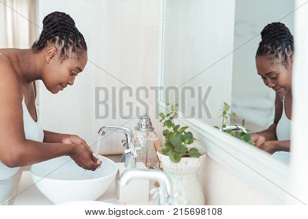 Young African woman standing over the sink in her bathroom washing her face with water in the morning