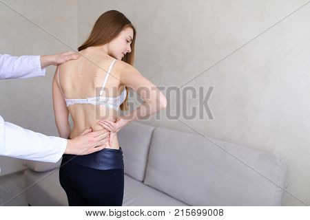 Professional male doctor advises and conducts examination of back of cute girl who has come to reception and feels discomfort in back. Guy physician with European-style with short haircut dressed in white medical uniform with stethoscope on neck, European