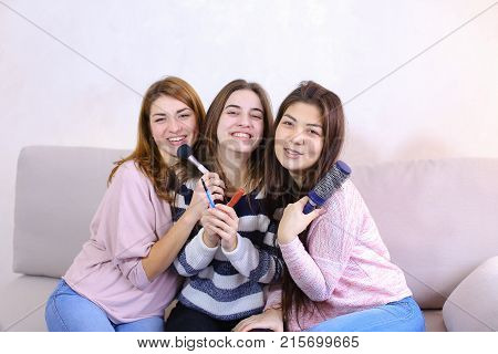 Charming young women look at camera lens and pose, smile and laugh, hold cosmetics and combs, beauty objects and sit on soft gray sofa in bright room in evening. One European-looking girl with medium-length blond hair dressed in pink blouse and jeans, sec