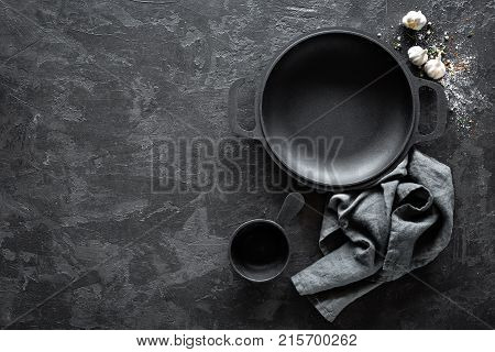 Empty cast-iron pan with cutlery on dark background for restaurant menu top view