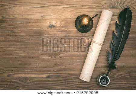 Scroll of paper page black feather pen and inkwell on table background. Education background with copy space. Writer desk table.