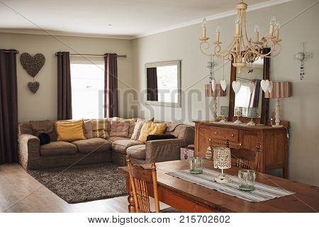 Interior of a contemporary suburban home decorated with country style dining table and chandelier with a modern sofa in the living room
