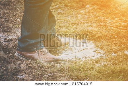 Feet of a person wearing lace up shoes and blue denim jeans standing in a puddle of water in short scrubby grass with golden glow from the sun