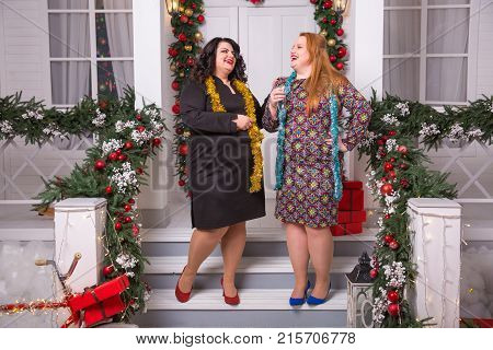Party and celebration. Winter holiday xmas. Christmas plus size woman New year girls staying on porch. sexy plus size woman