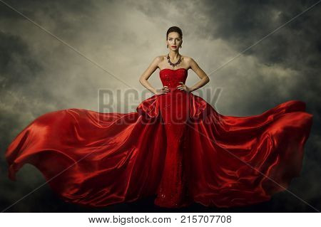 Fashion Model Art Dress Elegant Woman Standing in Red Retro Gown Silk Fabric Fluttering over Storm Sky Background