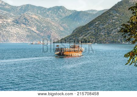 A tourist boat in the Bay of Kotor on the Adriatic Sea in the background of the Balkan mountains and two beautiful islands. Montenegro.