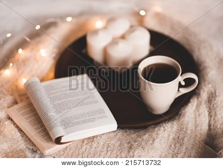 Cup of black tea with open book and candles on wooden tray and knitted sweater over Christmas lights. Good morning. Breakfast.