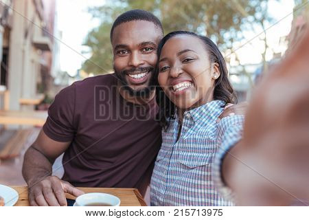 Happy young African couple sitting at table at a sidewalk cafe taking selfies while out on a date together