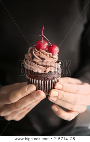 Woman holding tasty chocolate cupcake for Valentine's Day