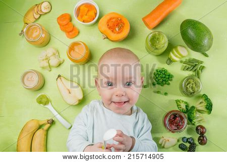 Smiling baby with baby food and ingredients. Healthy organic baby food concept. Starting solid food, delivery
