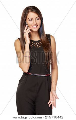 Businesswoman in black talking by the smartphone smiling over white background looking down and gesticulating