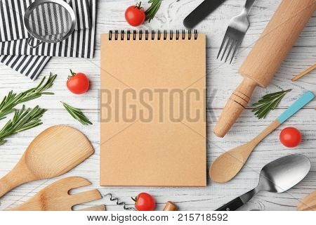 Notebook and various kitchen utensils on wooden background