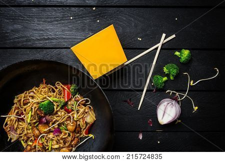 Wok. Udon Stir Fry Noodles With Chicken And Vegetables In Wok Pan On Black Wooden Background. With A