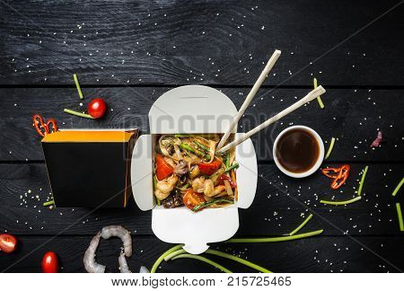 Wok. Udon Stir Fry Noodles With Seafood In A Box On Black Background. With Chopsticks And Sauce.