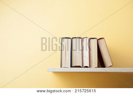 Stack of colorful books on wooden shelf. Education background. Back to school. Copy space for text.