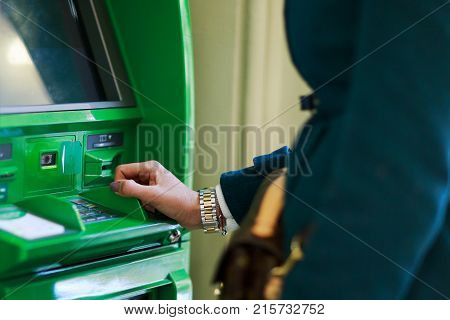 Photo of woman in coat at green cash machine in room