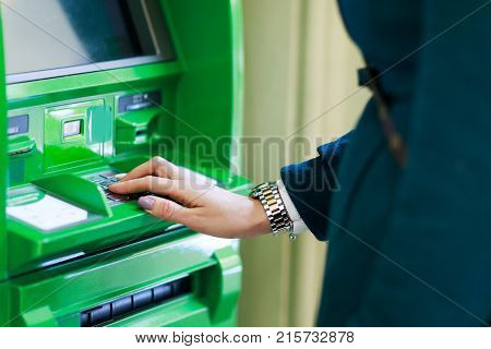 Picture of girl in coat at green cash machine in room