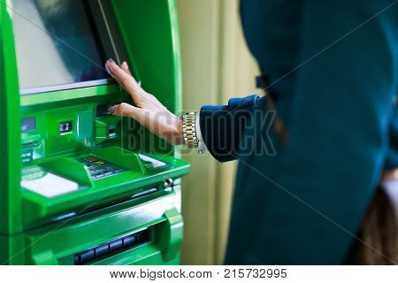 Photo of woman with clock on hand at green cash machine in room