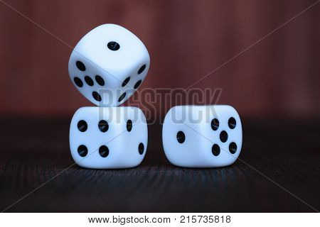 Stack of three white plastic dices on brown wooden board background. Six sides cube with black dots. Numbers 1 2 4 and 5.