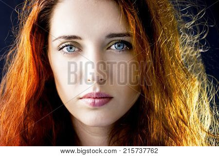 Portrait of a calm pensive young beautiful girl woman with long hair and blue eyes. Model posing in studio on dark background.