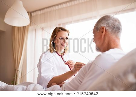 Health visitor and a senior man during home visit. A female nurse or a doctor examining a man.