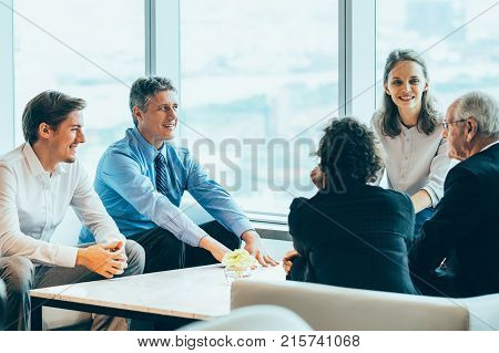 Closeup of five diverse business people discussing issues and sitting around table in lounge with big window in background