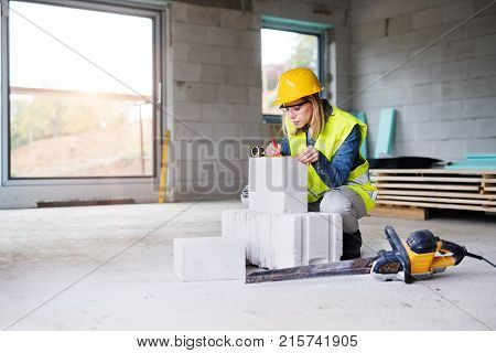 Female worker on the building site. Beautiful young woman measuring the building blocks. House construction.