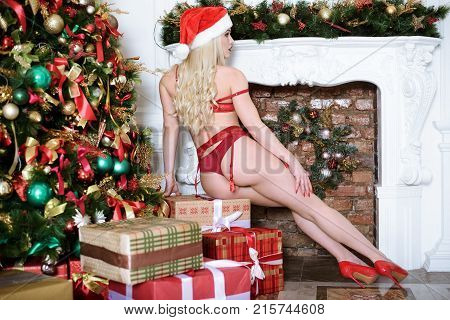 Blonde sexy Santa Clause in elegant panties, hat, shoes and bra. Fashion portrait of model girl indoors with Christmas tree. Cute woman in lace red lingerie. Female ass in underwear. Naked body