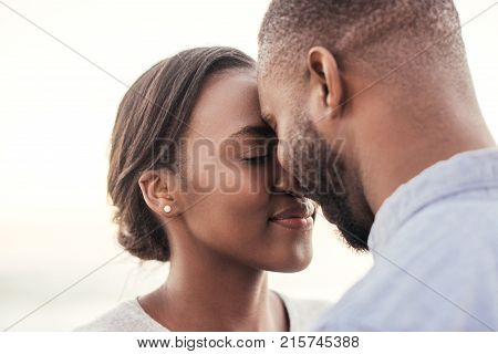 Content young African couple smiling and standing face to face while enjoying a late afternoon sunset together at the beach